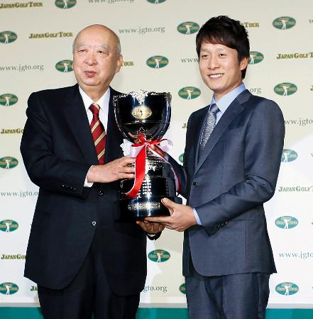最優秀選手賞に輝き、JGTOの海老沢勝二会長(左)から笑顔でトロフィーを受け取る金庚泰=7日、東京都内のホテル