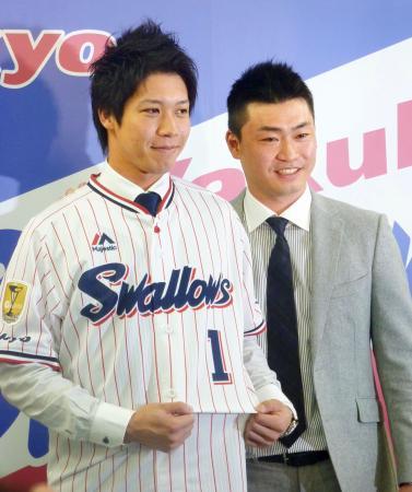 背番号1のユニホーム姿を披露したヤクルト・山田。右はマリナーズの青木宣親外野手=8日、東京都港区の球団事務所