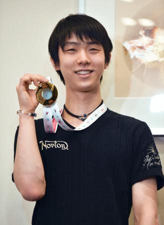 フィギュアスケートのグランプリファイナルから帰国し、金メダルを手に笑顔で記者会見する羽生結弦=15日午後、羽田空港