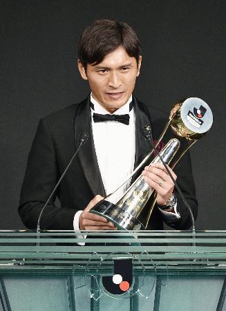 Jリーグの年間表彰式で、最優秀選手賞のトロフィーを手にあいさつする広島・青山敏弘=21日夜、東京都内のホテル