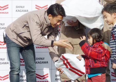 子どもたちにクリスマスプレゼントを手渡すドルトムントの香川真司=25日、宮城県岩沼市