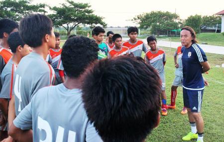 U―15カンボジア代表が練習するアカデミーで選手に話しかける北沢豪氏(右端)=11月、カンボジア南部タケオ州(JICA提供・共同)