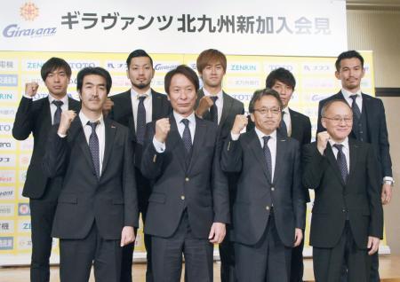 J2北九州の新体制を発表し、ポーズをとる柱谷監督(前列左から2人目)、元日本代表の本山(後列左端)ら=9日、北九州市
