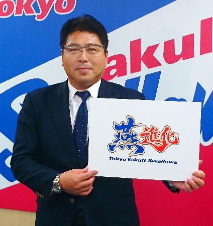 今季のスローガンが書かれたパネルを掲げるヤクルトの真中監督=12日、東京都港区