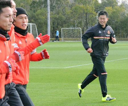 名古屋の今季初練習で、選手と一緒に体を動かす小倉新監督(右)=愛知県豊田市