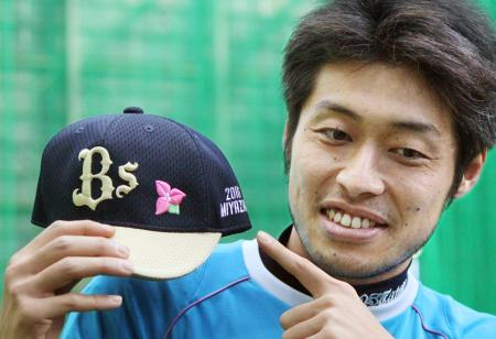 宮崎キャンプで着用する帽子を手にするオリックスの佐藤達=神戸市