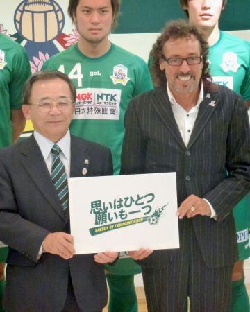 記者会見で宮田博之社長(左)とチームスローガンを手にするJ2岐阜のラモス瑠偉監督=21日、岐阜市