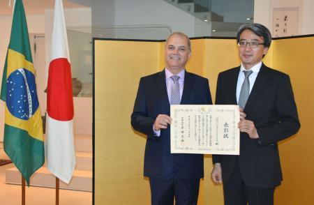 26日、リオデジャネイロの日本総領事公邸で、山元毅総領事(右)から外務大臣表彰の表彰状を受け取ったブラジル柔道連盟のテイシェイラ会長(共同)