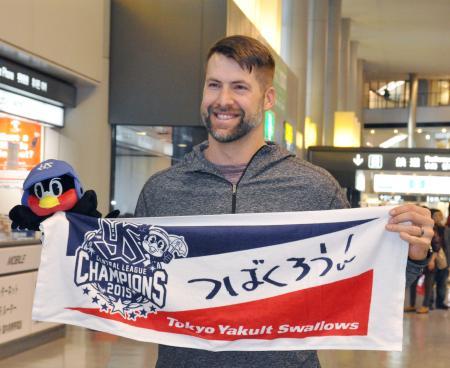 来日し、球団グッズを手にポーズをとるヤクルトの新外国人デイビーズ=28日、成田空港