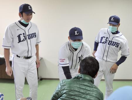 国立精神・神経医療研究センターを訪問し、利用者と握手する西武の高橋朋。左は上本、右は星=28日、東京都小平市