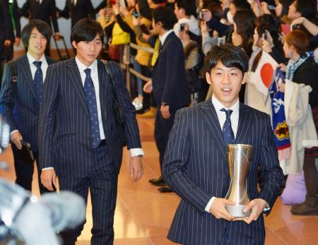 サッカーのアジア選手権で優勝し、笑顔で帰国した遠藤(右)らU―23の日本代表=31日夜、羽田空港
