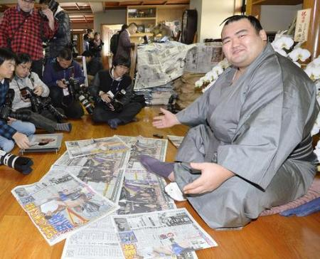 初優勝を報じるスポーツ紙を前に笑顔の大関琴奨菊=千葉県松戸市の佐渡ケ嶽部屋(2016年1月25日、共同)