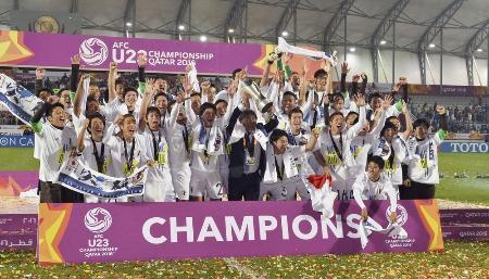 韓国を破って優勝し、セレモニーで大喜びの手倉森監督(前列中央)と日本イレブン=1月30日、ドーハ(共同)