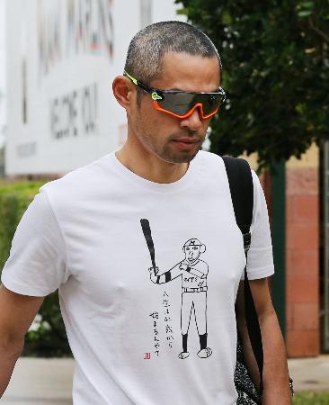 「人生は42歳から始まるんやて」と書かれたTシャツを着てキャンプインするマーリンズのイチロー=ジュピター(共同)