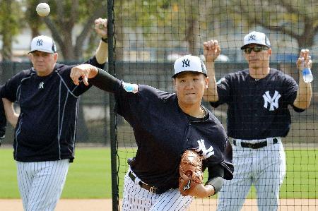 ジラルディ監督(右)らが見守る中、マイナーの打者を相手に投球するヤンキース・田中=タンパ(共同)