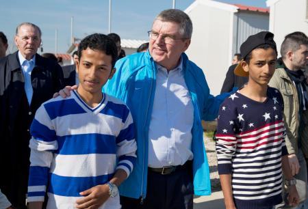 アテネの難民キャンプを訪問し、難民と歩くIOCのバッハ会長(中央)=1月(AP=共同)