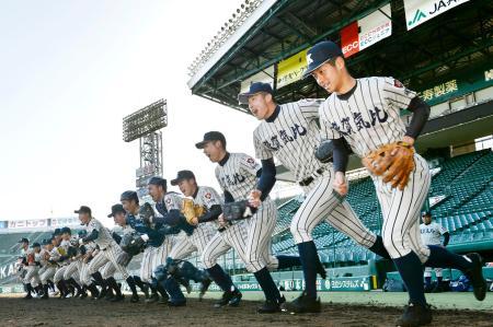 選抜高校野球の甲子園練習が始まり、グラウンドへ駆けだす敦賀気比ナイン=甲子園