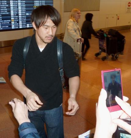 帰国し、ファンにサインをするサッカー日本代表の岡崎慎司=21日午前、羽田空港