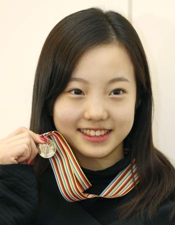 フィギュアスケートの世界ジュニア選手権から帰国し、メダルを手に笑顔の本田真凜=22日午前、羽田空港