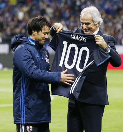 国際Aマッチ通算出場を100試合とし、ハリルホジッチ監督(右)から記念のユニホームを受け取る岡崎=埼玉スタジアム