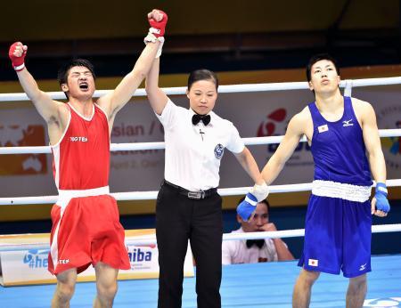 男子ライト級準決勝でモンゴル選手(左)に敗れた成松大介=中国・遷安(共同)