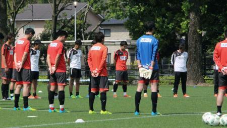 全体練習再開を前に黙とうするJ2熊本の選手たち=2日、熊本市
