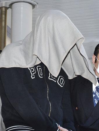 布をかぶり、移送される笠原将生容疑者=4月29日、羽田空港