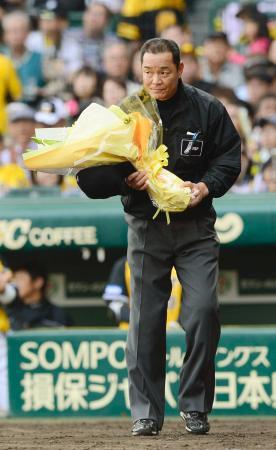 阪神―ヤクルト7回戦で通算2500試合出場を達成し、花束を手にする東利夫審判員=甲子園