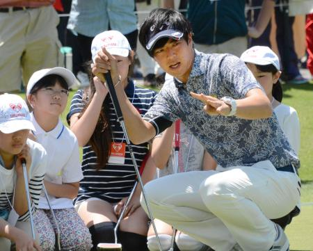 ゴルフの慈善大会「ザ・レジェンド・チャリティー」で、福島県相馬市から招待した小学生にパットの指導をする石川遼=千葉県の麻倉GC