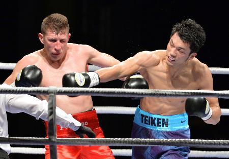 4回、フェリペ・サントス・ペドロソ(左)にパンチを浴びせる村田諒太。この後TKO勝ちした=香港(共同)