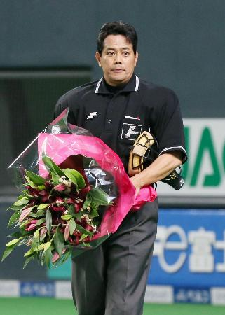 日本ハム―西武11回戦で通算1500試合出場を達成し、花束で祝福される西本欣司審判員=札幌ドーム