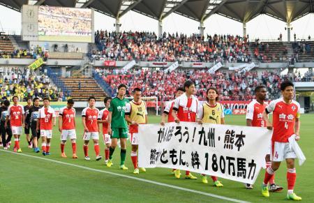 地震から約1カ月で公式戦に復帰し、試合後に横断幕を持ってピッチを一周するサッカーJ2熊本のイレブン=15日、千葉市のフクダ電子アリーナ