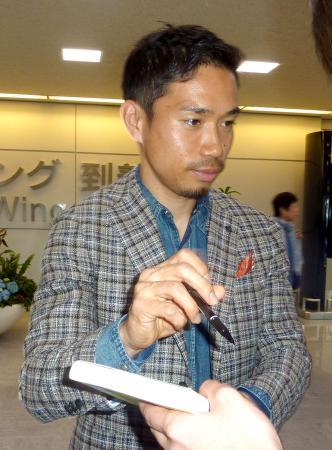 シーズンを終えて帰国し、ファンにサインするインテル・ミラノの日本代表DF長友佑都=19日午前、成田空港