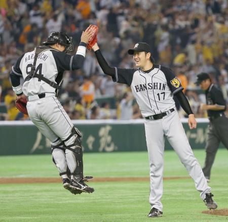 プロ初完封勝利を挙げ、捕手原口とハイタッチする阪神・岩貞=東京ドーム