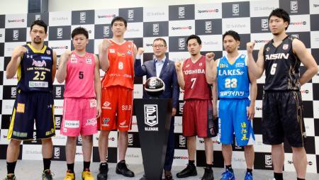 Bリーグの日程の発表記者会見で、ポーズをとる大河正明チェアマン(中央)と各チームの選手たち=10日、東京都北区