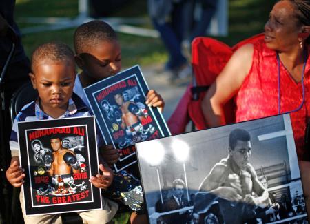 10日、米南部ケンタッキー州ルイビルでムハマド・アリ氏の生前の写真を掲げる子どもたち(ロイター=共同)