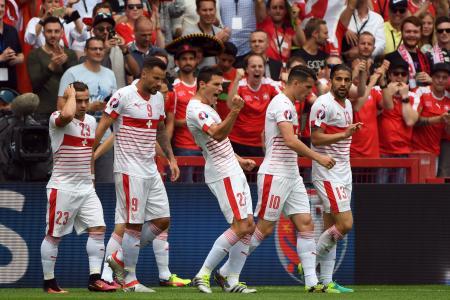 拳を握りしめて得点を喜ぶシェア(中央)らスイスの選手たち=11日、ランス(AP=共同)