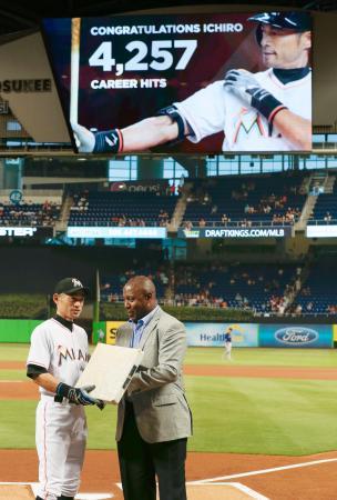試合前、日米通算4257安打を祝福するセレモニーで、マイケル・ヒル編成本部長(右)から二塁ベースを手渡されるマーリンズのイチロー=マイアミ(共同)
