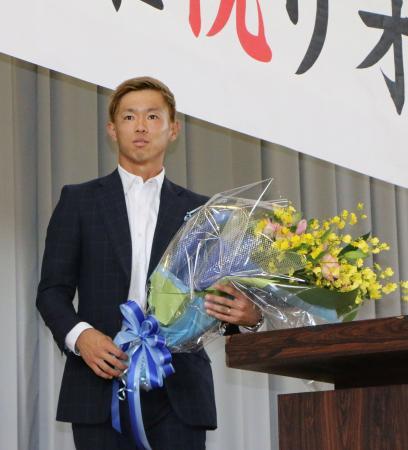 リオ五輪のサッカー男子代表にOA枠で選ばれ、母校・徳島商高の壮行会で花束を手にする広島の塩谷=20日、徳島市