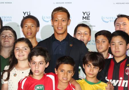 22日、米ワシントンで開かれた式典で、子どもたちに囲まれるサッカー日本代表の本田圭佑選手(共同)