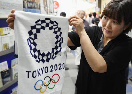 2020年東京五輪・パラリンピックの大会エンブレムを使った公式オリジナル商品を手にする女性=23日午前、東京都庁