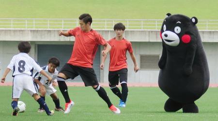 小学生や「くまモン」とプレーするサッカー日本代表の香川真司(左から3人目)=26日、兵庫県三木市