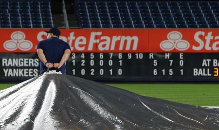 ヤンキース―レンジャーズ戦が雨で中断し、球場にシートを掛けるグラウンドキーパー=ニューヨーク(AP=共同)