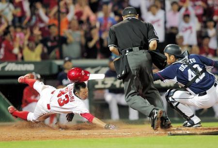 14日の西武戦で9回に本塁を突く広島の二走菊池(左)。アウトと判定されるが「コリジョンルール」が適用されサヨナラの生還となる。捕手上本=マツダ