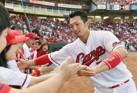 2試合連続のサヨナラ本塁打を放ち、ファンとタッチする広島・鈴木=マツダ