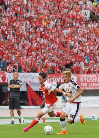 本拠地うまかな・よかなスタジアムで開催されたホームゲームで、C大阪・山口(右)と競り合う熊本・清武。来場したファンでメインスタンドがチームカラーの赤に染まった=3日