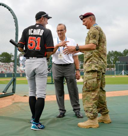 試合前、米軍兵士と話をするマーリンズのイチロー外野手(左)。中央はMLBの競技運営最高責任者で前ヤンキース監督のトーリ氏=3日、フォートブラッグ(共同)