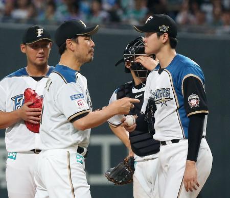 7回、指のまめをつぶし、マウンドで吉井コーチ(手前左)と話す日本ハム・大谷。治療に戻りそのまま降板となる=札幌ドーム