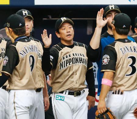 球団新記録となる15連勝を飾り、ナインを迎える日本ハムの栗山監督(中央)=京セラドーム