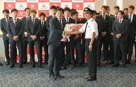 ブラジルへ出発を前に、激励の花束を受け取るサッカー男子のリオ五輪代表の手倉森誠監督(手前左)=21日午前、羽田空港